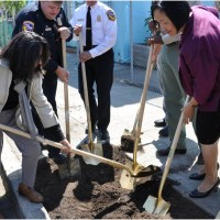 Sandy Macias and Oakland Mayor Jean Quan plant a ceremonial tree.