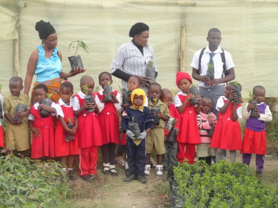 Children in Zimbabwe hold the tree they will plant.